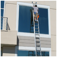Second story window of a commercial building in Roseville, CA being cleaned by a man on ladder.